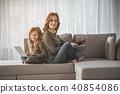 Mom and kid sitting with laptops and laughing at home 40854086