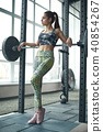 Young woman exercises in gym healthy lifestyle leaning on barbell 40854267