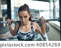 Young woman exercises in gym healthy lifestyle pulling weights 40854269