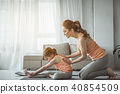 Red-haired mother and kid training in living room 40854509