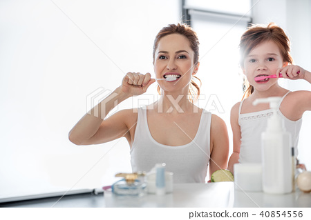 Mother and daughter brushing teeth in bathroom 40854556