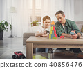 Joyful parent and kid playing at home together 40856476