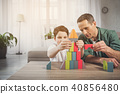 Cheerful father and son constructing tower from blocks at home 40856480