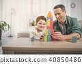Glad father and son constructing house from small details 40856486