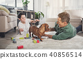 Happy father and son playing with dog at home 40856514