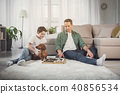 Cheerful father and boy playing checkers at home 40856534