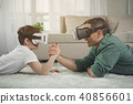 Carefree parent and kid competing in arm wrestling with gadgets 40856601