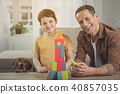 Happy father and son with puppy playing in house 40857035