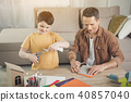 Cheerful parent and child folding figures from papers 40857040