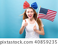 Happy young woman holding an American flag 40859235