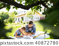 Father with a small daughter outside, planning wooden birdhouse. 40872780