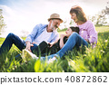 Senior couple with grandaughter outside in spring nature, relaxing on the grass. 40872862