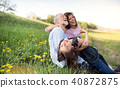 Senior couple with grandaughter outside in spring nature, relaxing on the grass. 40872875
