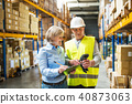 Senior woman manager and man worker working in a warehouse. 40873063