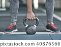 Young woman exercises in gym healthy lifestyle holding dumbbell close-up 40876566