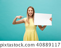 Portrait of young woman in yellow dress pointing finger at side white blank board. Isolated over 40889117