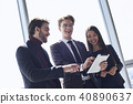 Businesspeople at office working together standing browsing digital tablet cheerful 40890637