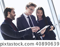Businesspeople at office working together standing discussing application on digital tablet cheerful 40890639
