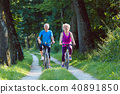 Happy and active senior couple riding bicycles outdoors in the park 40891850