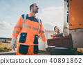 Two refuse collection workers loading garbage into waste truck 40891862