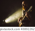 Bearded man playing bass guitar with spotlight 40892262