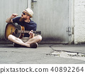 Bearded man playing acoustic guitar and smoking cigar 40892264