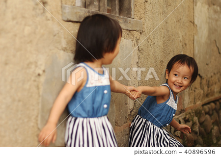一對亞洲雙胞胎女孩在土角厝的牆邊手牽手玩耍 40896596