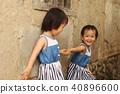 一对亚洲双胞胎女孩在土角厝的墙边手牵手玩耍 40896600