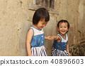 一對亞洲雙胞胎女孩在土角厝的牆邊手牽手玩耍 40896603
