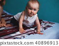 Baby girl crawling at bed in living room 40896913