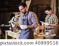 Inspector and carpenter discuss the process of making wood products for furniture 40899516
