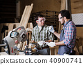 Two men builder with circular saw having a conversation 40900741