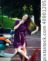 Fashion woman in checkered dress posing and pulling her hair near scooter over summer park 40901205