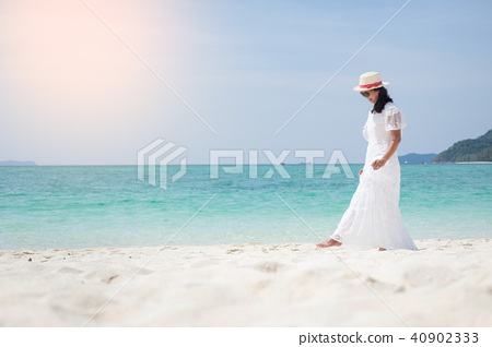 a beautiful carefree Woman relaxing at the beach enjoying her su 40902333