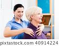 Masseuse applying neck massage on older woman  40914224