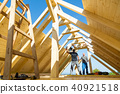 Builders at work with wooden roof construction. 40921518