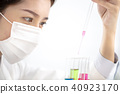 asian female scientist looking at test tube 40923170
