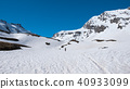 Alpinist hiking ski touring on snowy slope 40933099