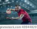The table tennis player serving 40944820
