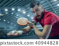 The table tennis player serving 40944828