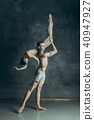 The young modern ballet dancers posing on gray studio background 40947927
