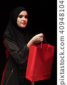 Portrait of beautiful smart young muslim woman wearing black hijab offering shopping bag as shop 40948104