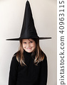 Smiling little blond girl in black witch costume 40963115