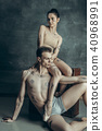The young modern ballet dancers posing on gray studio background 40968991