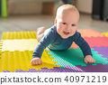 Infant baby boy playing on colorful soft mat. Little child making first crawling steps on floor. Top 40971219