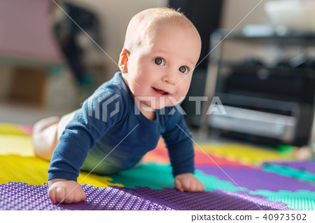 Infant baby boy playing on colorful soft mat. Little child making first crawling steps on floor. Top 40973502