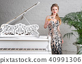 Blonde lady with glass of wine near white piano 40991306
