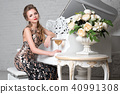 Blonde lady with glass of wine near white piano 40991308