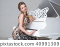 Blonde lady with glass of wine near white piano 40991309