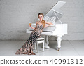 Blonde lady with glass of wine near white piano 40991312